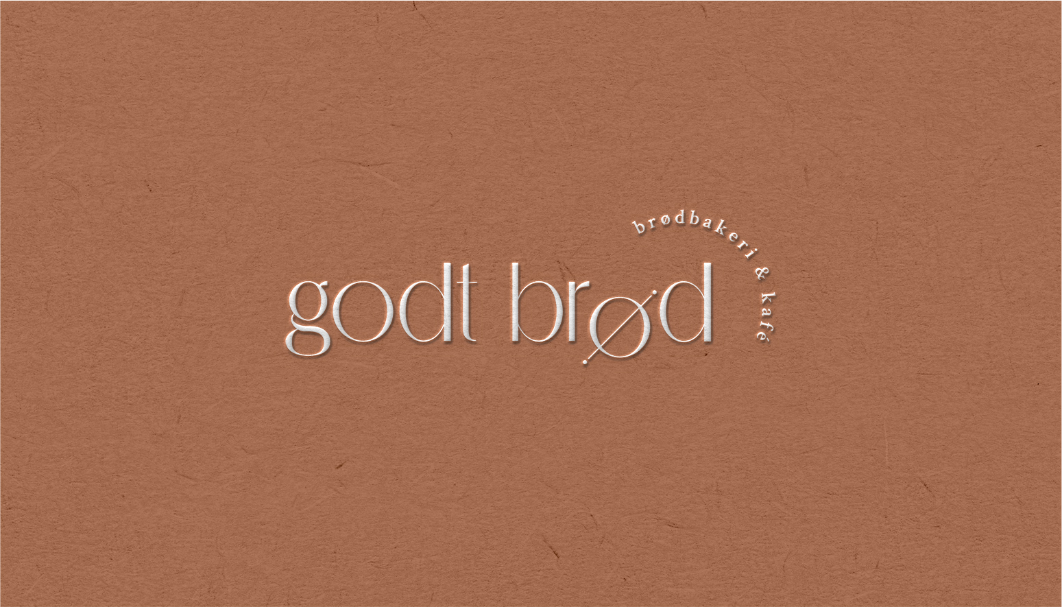 Close up of a burnt orange business card with the Godt Brod logo in the middle