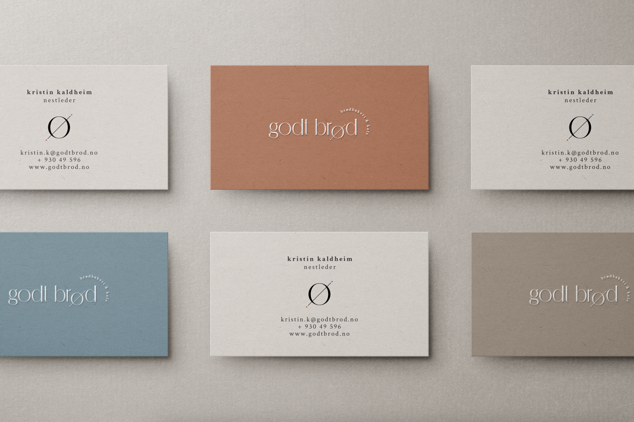 Six Godt Brod business cards in muted blue, burnt orange and beaver brown.