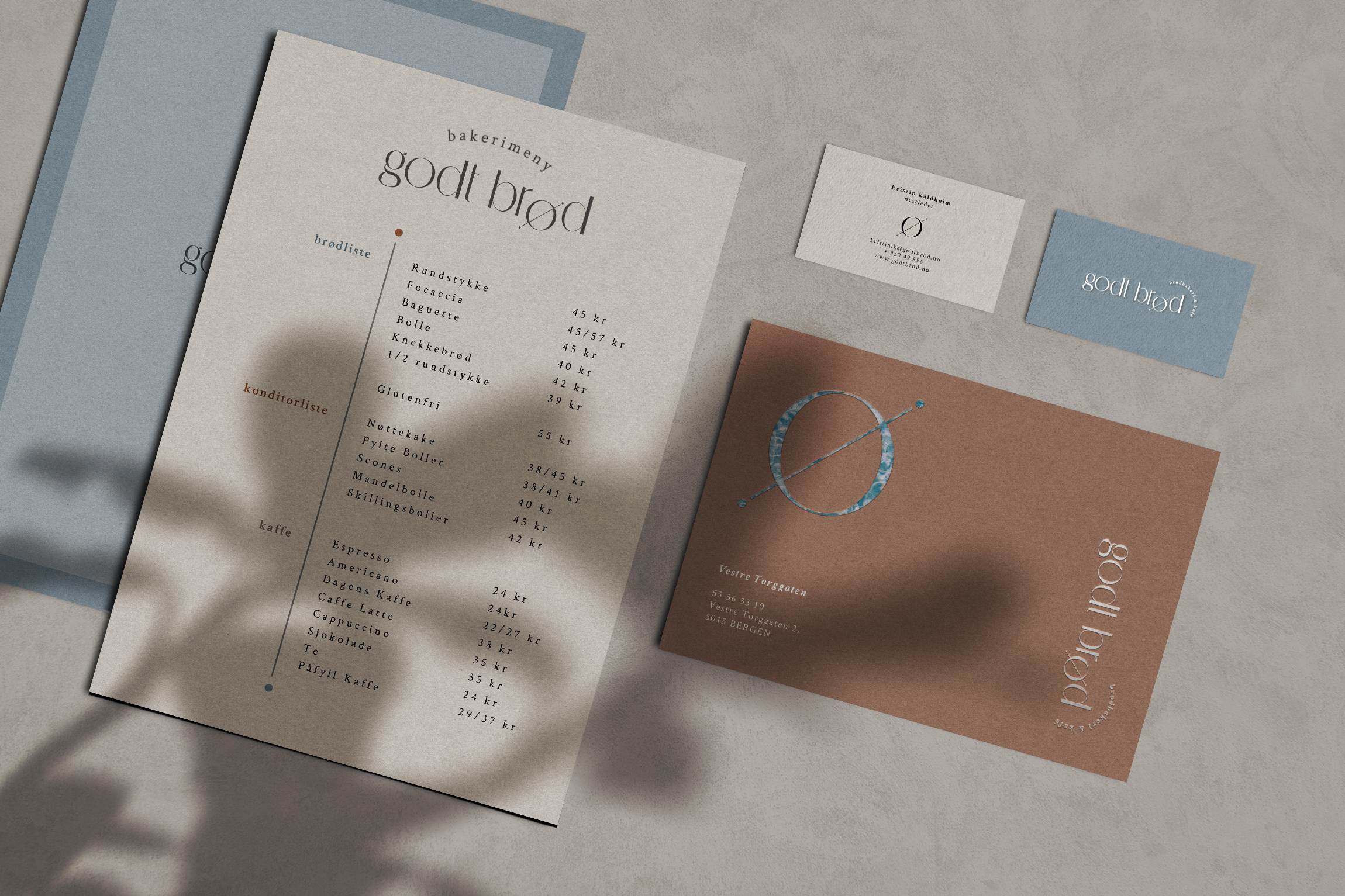 Overhead shot of the bakery cafe menu, two business cards and postcard