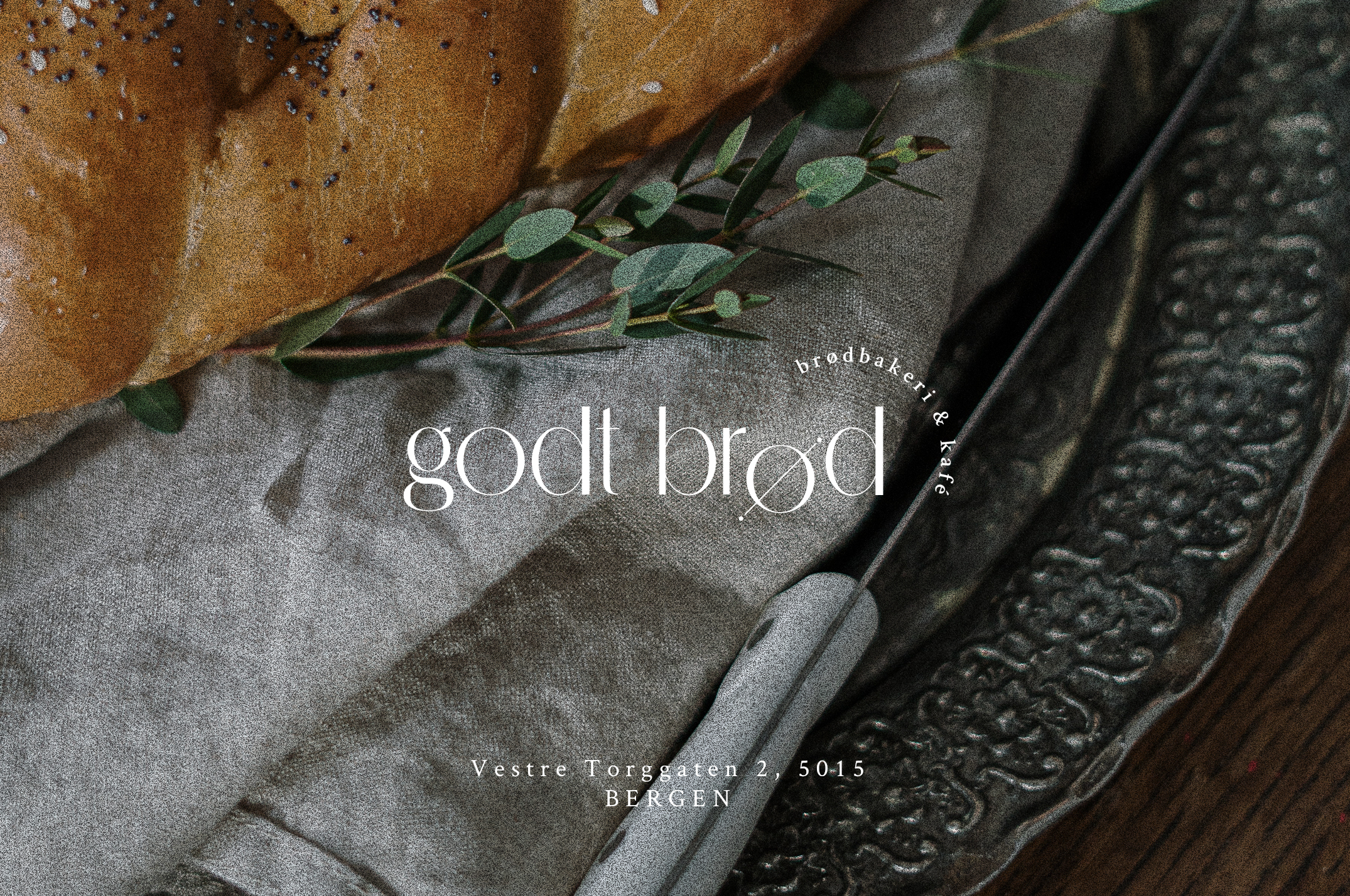 Close up of a piece of poppy bread on a light grey cloth, an angled bread knife and vintage silver platter. A white Godt Brod logo is centered on top of the image.